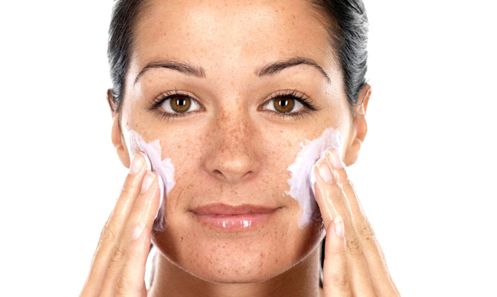 woman exfoliates face
