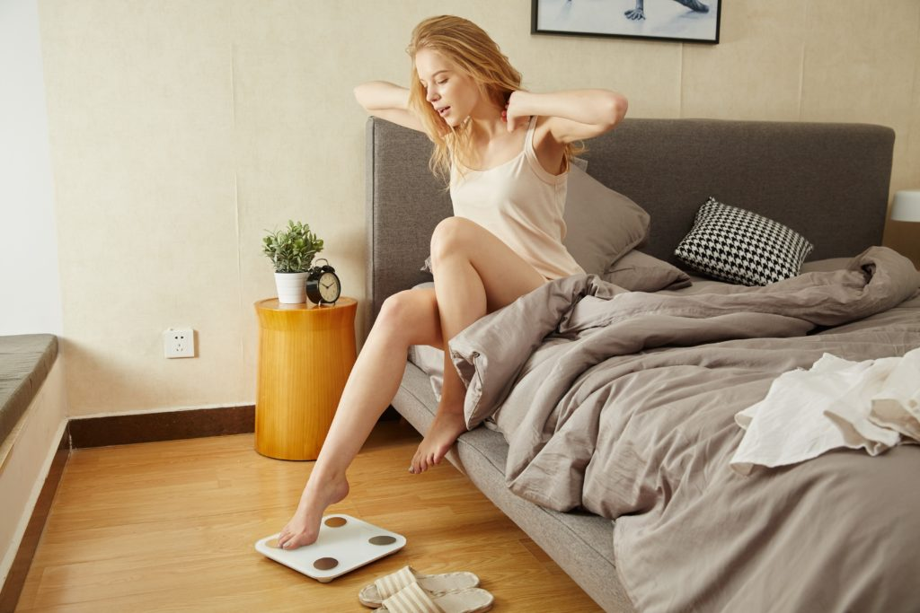 woman sitting on a bed, stretching