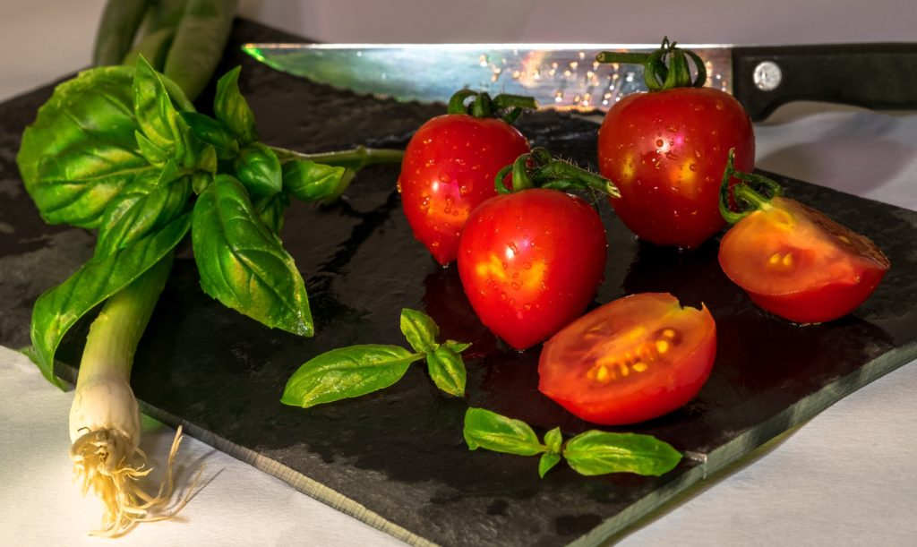 Red tomatoes on cutting board.