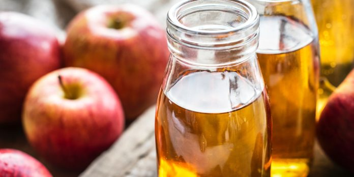 A picture of apples and some apple cider vinegar