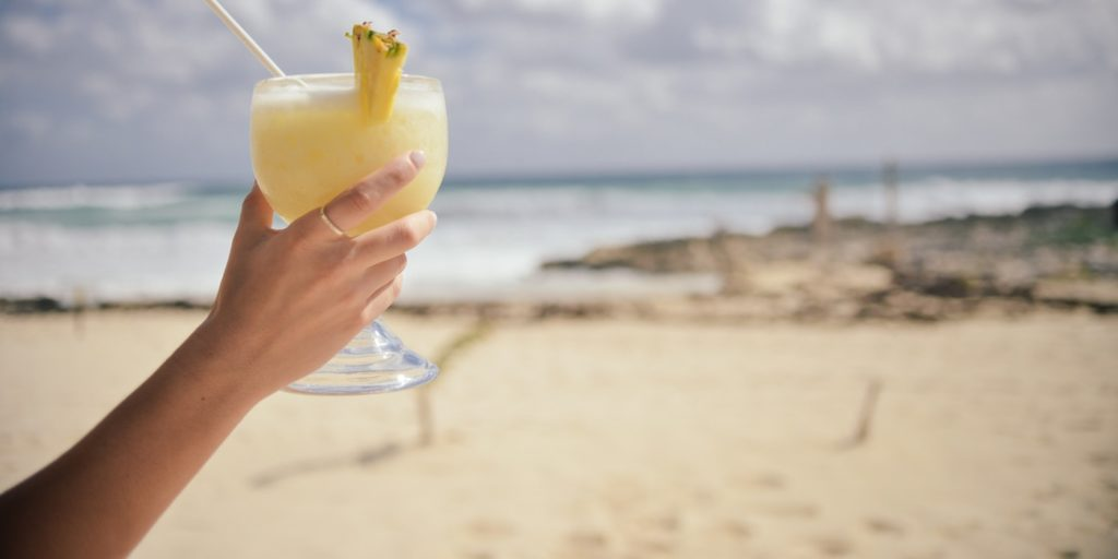 A person holding a glass of pineapple juice