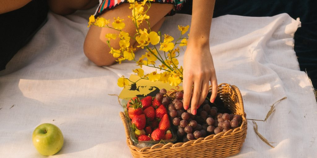 Picking a fruit from a basket